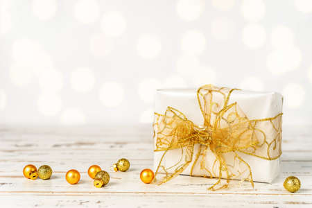 White Christmas gift box with big golden bow on white background. Copy space Stockfoto