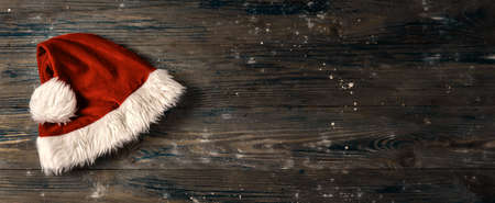 Top view of Santa's hat on dark wooden background in rustic style