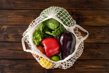 Vegetables in reusable cotton net bag on dark rustic background. Zero waste concept