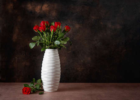 Red roses in a white vase against dark background for Valentine's Day. Copy space
