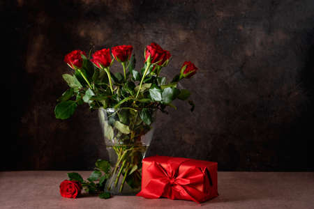 Red roses in a glass vase against dark background for Valentine's Day. Vintage style. Copy space