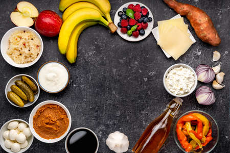 Variety probiotic and prebiotic foods captured from above on black background with copy space. Healthy products for strong immunity and intestine microbiome Imagens