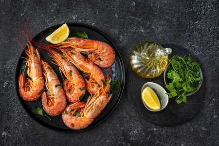 Top view of dining table with red big prawns and coocking ingredients