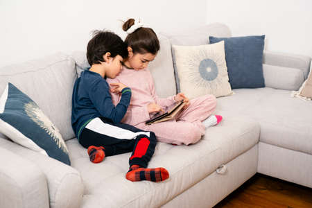 Two kids sitting on sofa with tablet. Real life, diversity, digintal technology