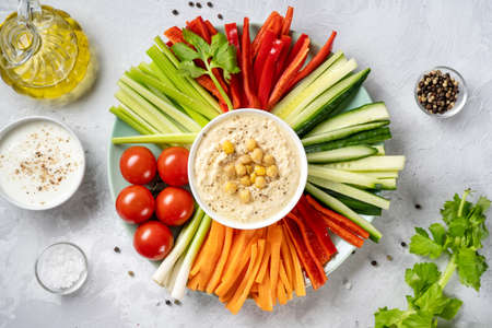 Plate with assorted fresh vegetable sticks with dips
