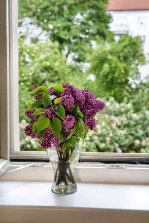 Close up of a vase with beautiful purple lilac flowers at the open window in spring time. Good moments, reducing stress concept