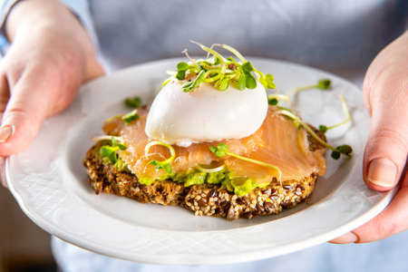Unrecognisable woman in blue shirt holds a plate with salmon toast, avocado and posched egg. Close up. Healthy vegetarian breakfast food. Brain food concept.