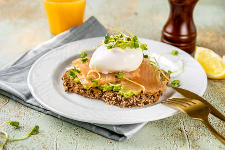 A home-made toast with mashed avocado, salmon, poached egg and microgreens in a plate. Healthy food concept. Omega 3 fats. Brain food