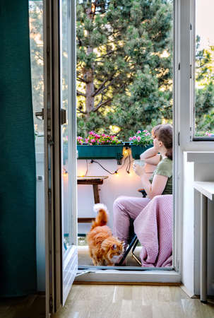 Young woman is relaxing at balcony at the evening. Regenerative travel. Self care and breathing therapy. Home comfort zone and mental health concept. Holistic rest