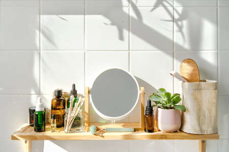 Shelf in bathhroom with zero waste cosmetic items and reusable bottles. Shadows from the window. Wellness and sustainability concept