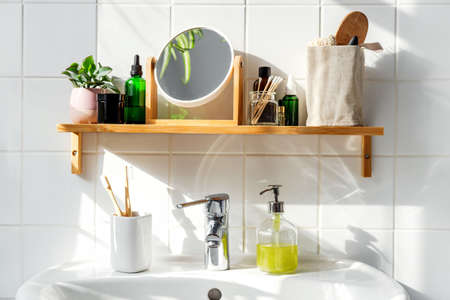 Shelf in bathroom with sustainble cosmetic items and reusable bottles. Shadows from the window. Wellness and sustainability concept