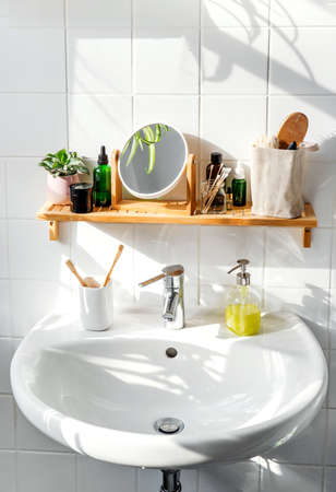 Shelf in a bathroom over the sink with sustainable cosmetic items and reusable bottles. Shadows from the window. Wellness and sustainability concept
