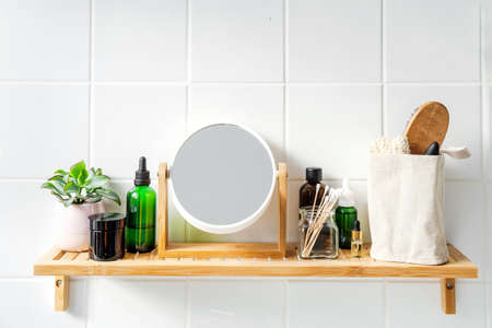 Close up of bamboo shelf in a bathroom with stainable organic cosmetics and reusable bottles and conatiners. Wellness and sustainability concept