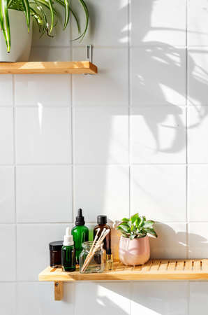 Bamboo shelfs on white wall with sustainable cosmetics and plants in a bathroom. Wellness and sustainability concept. Shadows on the wall. Copy space