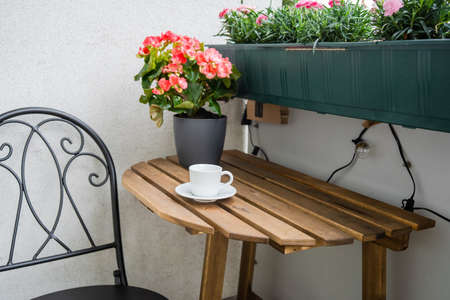 Close up of wooden table with cup of coffee at balcony. Comfort home zone