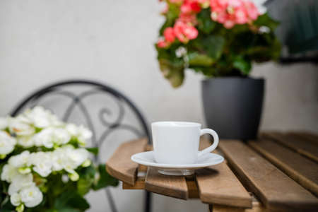 Cup of coffee on a table at cosy balcony with flowers. Comfort zone. Home gardening. Stress reducing concept