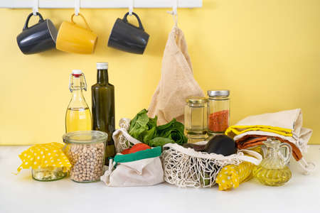 Eco-friendly reusable wax cloth, cotton bags, glass bottles at the kitchen. Zero waste concept. Sustainable living. Bright yellow background