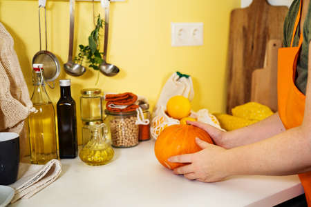 Unrecognisable woman in orange apron holding pumpkin in her hands. Illuminating yellow background. Autumn concept. Sustainalbe lifestyle. Pumpking cooking