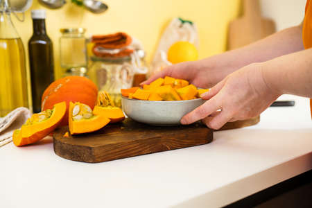 Close up of female hands place a plate with raw pumpkin pieces on table. Autumn concept. Sustainalbe lifestyle