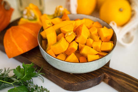 Close up of a plate with raw pumpkin pieces on kitchen table. Positive yellow backgorund. Autumn concept. Thanksgiving day