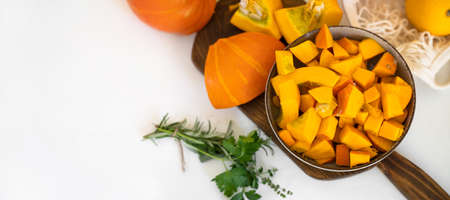 Top view of a plate with raw pumpkin pieces on kitchen table. Long banner wth copa space. Autumn concept. Thanksgiving day