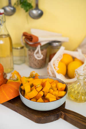 A plate with raw pumpkin pieces on kitchen table. Positive yellow backgorund. Autumn concept. Thanksgiving day
