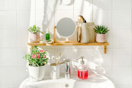 Bamboo shelf with toiletries in white modern bathroom with a sink next to a window at sunny day. Shadows on the white tile wall. Zero waste and sustainable life style. Wellness