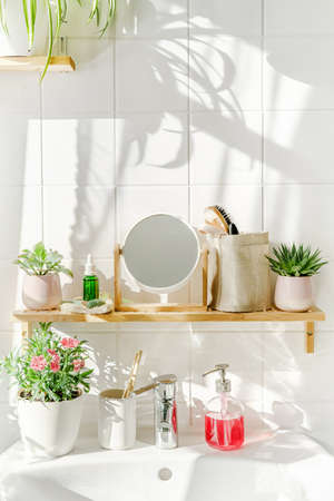Bright and white modern bathroom with bamboo shelf and a sink next to a window at sunny day. Shadows on the white tile wall. Zero waste and sustainable life style. Wellness