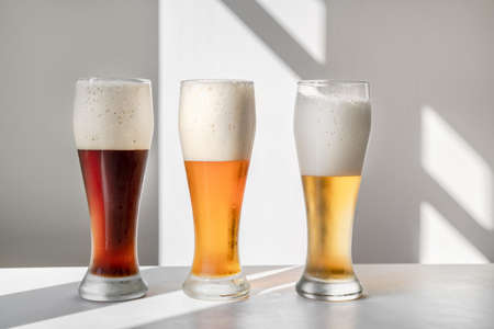Three glasses of different sorts of beer on white background with graphic shadows. Minimalistic composition with natural light. Oktoberfest. Copy space