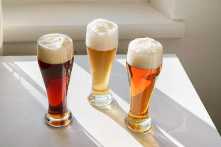 Top view of three glasses with different sorts of beer on white table in front of the window. Natural light. Life style concept. Oktoberfest holiday