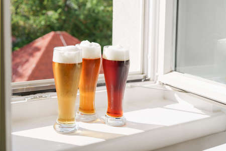 Glasses with beer on windowsill and open window at sunny day. Natural light. Oktoberfest. New normal and life style concept