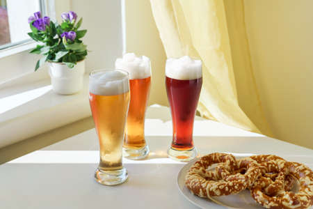 Three glasses with different sorts of beer and pretzels on table next to window. Natural light at sunny day. Oktoberfest concept Stock Photo