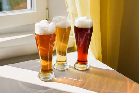 Different sorts of beer in long glasses on table next to window. Natural light at sunny day. Shadows on table. Oktoberfest concept. New normal