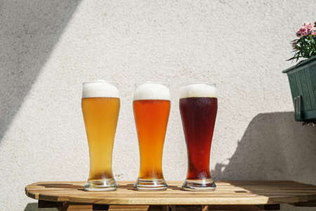 Different sorts of beer in long glasses on wooden table at balcony. Natural light at sunny day. Graphic shadows on the wall. Oktoberfest concept. New normal Stock Photo
