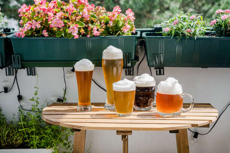 Beer glasses on wooden table at green balcony with plants and flowers on sunny day. Oktoberfest concept. New normal