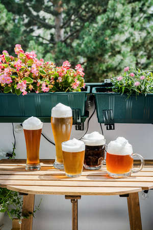 Many sorts of beer in glasses on wooden table at green balcony on sunny day. Oktoberfest concept. New normal Stock Photo