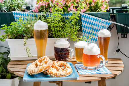 Close up of many beer glasses on wooden table at green balcony. Celebration of Oktoberfest in new normal conditions