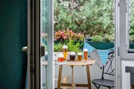 Wooden table with beer glasses on green balcony. Oktoberfest celebration in new normal Stock Photo