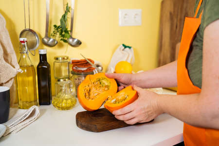 Unrecognisable woman in orange apron preparing halved raw pumpkin for cooking. Bright yellow background. Autumn concept. Sustainalbe lifestyle