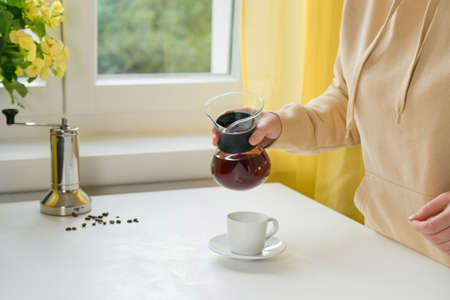 Unrecognisable woman pouring filter espresso from glass coffee maker into a cup. Comfort home zone. Making hot coffee. Autumn concept