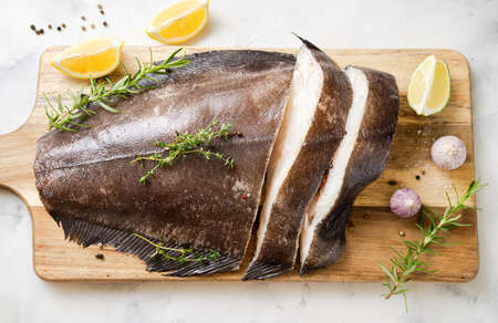 Close up of fresh raw halibut fish on wodden board with herbs and lemon. Top view. Omega 3 fats good for mental clarity. Brain food Stock Photo
