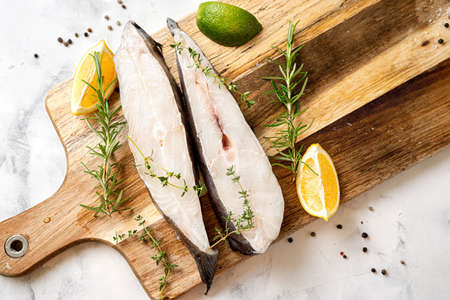 Top view of fresh and raw halibut fish steaks with herbs and lemon on wooden board. Omega 3 fats good for mental clarity. Brain food