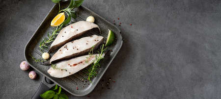 Raw halibut fish steaks with herbs and lemon prepared for cooking in a grill pan. Long banner with copy space. Healthy omega 3 unsaturated fats good for brain and mental clarity Stock Photo