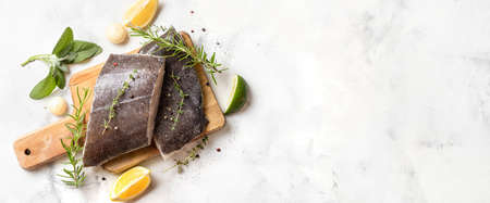 Top view of two raw halibut fish steaks with herbs and lemon on wooden board and white background. Long banner with copy space. Omega 3 fats good for mental clarity. Brain food Stock Photo