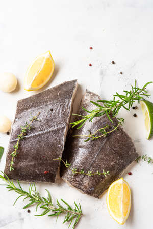 Top view of two fresh halibut raw steaks with herbs and lemon on white background. Omeag 3 fats. Brain food