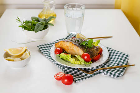 Close up of crispy grilled halibut steak on a plate and dining table prepared for lunch. Healthy food rich of omega unsaturated fats good for brain health Stock Photo