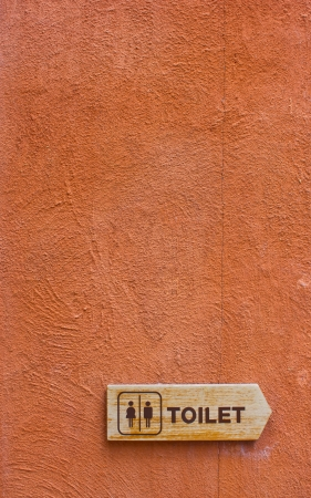 Wooden Toilet Sign on The Orange Wall  photo