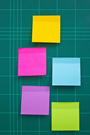 Colorful sticky notes on cutting mat   photo