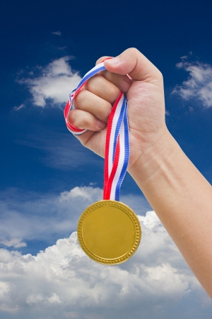 Golden medal in man s hand isolated with blue sky   photo