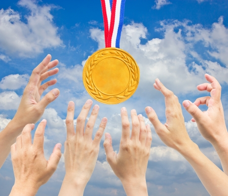Hands with golden medal in front of blue sky    photo